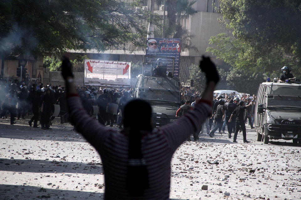 Photo -   Egyptian security forces, background, clash with protesters near Tahrir Square in Cairo, Egypt, Sunday, Nov. 25, 2012. Supporters and opponents of Egypt's president grow more entrenched in their potentially destabilizing battle over the Islamist leader's move to give himself near absolute powers, with neither side appearing willing to back down. (AP Photo/Ahmed Gomaa)