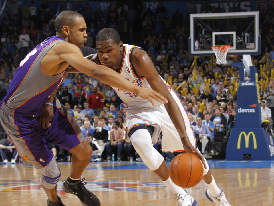 Photo - Oklahoma City Thunder small forward Kevin Durant (35) drives against Phoenix Suns small forward Grant Hill (33) during the NBA basketball game between the Oklahoma City Thunder and the Phoenix Suns at the Chesapeake Energy Arena on Wednesday, March 7, 2012 in Oklahoma City, Okla.  Photo by Chris Landsberger, The Oklahoman