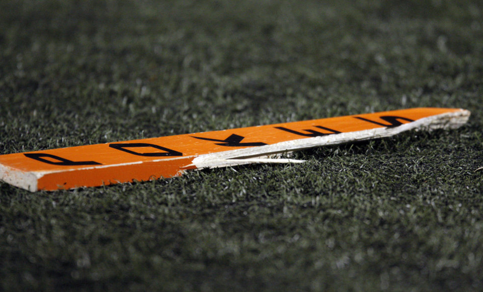 Photo - A broken OSU fan's paddle fell to the sideline during the Bedlam college football game between the University of Oklahoma Sooners (OU) and the Oklahoma State University Cowboys (OSU) at Boone Pickens Stadium in Stillwater, Okla., Saturday, Nov. 27, 2010. OU won, 47-41. Photo by Nate Billings, The Oklahoman  NATE BILLINGS