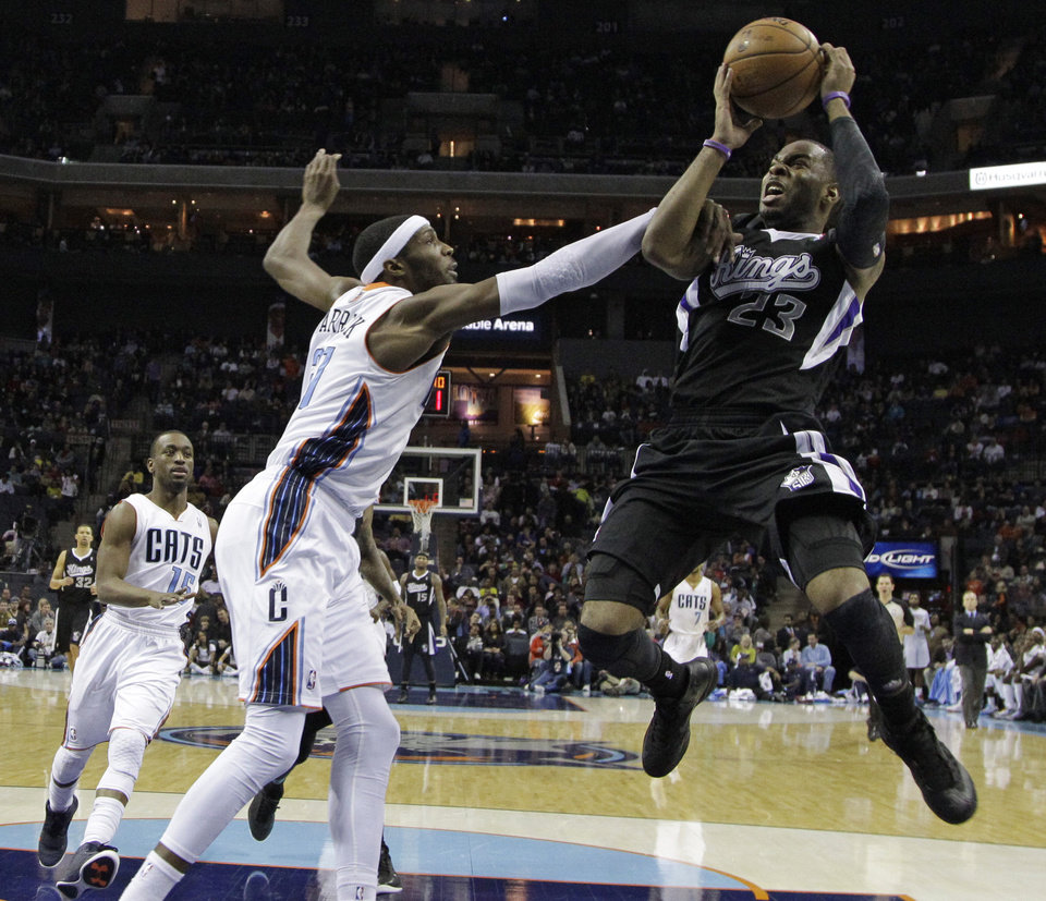 Sacramento Kings\' Marcus Thornton, right, is fouled by Charlotte Bobcats\' Hakim Warrick, left, during the first half of an NBA basketball game in Charlotte, N.C., Saturday, Jan. 19, 2013. (AP Photo/Chuck Burton)
