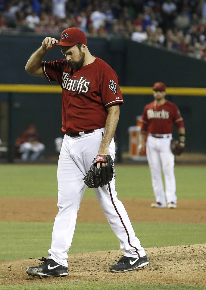 Photo - Arizona Diamondbacks' Josh Collmenter, left, walks off the pitcher's mound with his head down after giving up a 2-run home run to Los Angeles Dodgers' Adrian Gonzalez as Diamondbacks' Martin Prado, right, looks on during the third inning of a baseball game on Sunday, May 18, 2014, in Phoenix. (AP Photo/Ross D. Franklin)