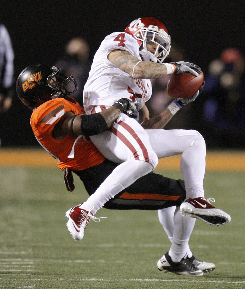 Photo - Oklahoma's Kenny Stills (4) is brought down by Oklahoma State's Brodrick Brown (19) during the Bedlam college football game between the Oklahoma State University Cowboys (OSU) and the University of Oklahoma Sooners (OU) at Boone Pickens Stadium in Stillwater, Okla., Saturday, Dec. 3, 2011. Photo by Bryan Terry, The Oklahoman