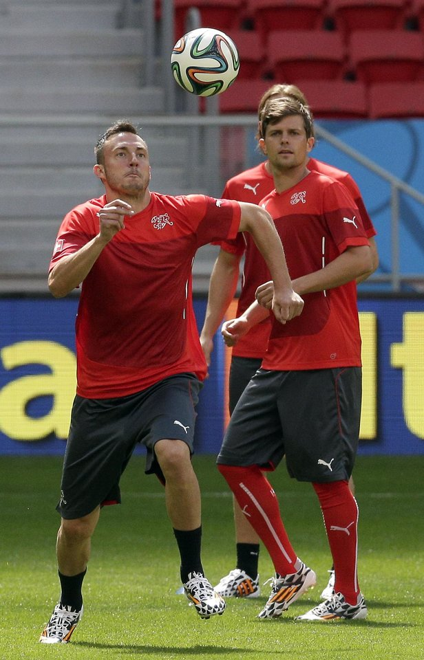 Photo - Switzerland's Josip Drmic, left, plays the ball during an official training session the day before the group E World Cup soccer match between Switzerland and Ecuador at the Estadio Nacional in Brasilia, Brazil, Saturday, June 14, 2014.  (AP Photo/Michael Sohn)