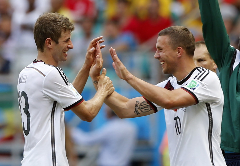 Germany's Thomas Mueller, left, is greeted by Lukas Podolski after being substituted after scoring a hat-trick during the group G World Cup soccer match between Germany and Portugal at the Arena Fonte Nova in Salvador, Brazil, Monday, June 16, 2014.  (AP Photo/Matthias Schrader)