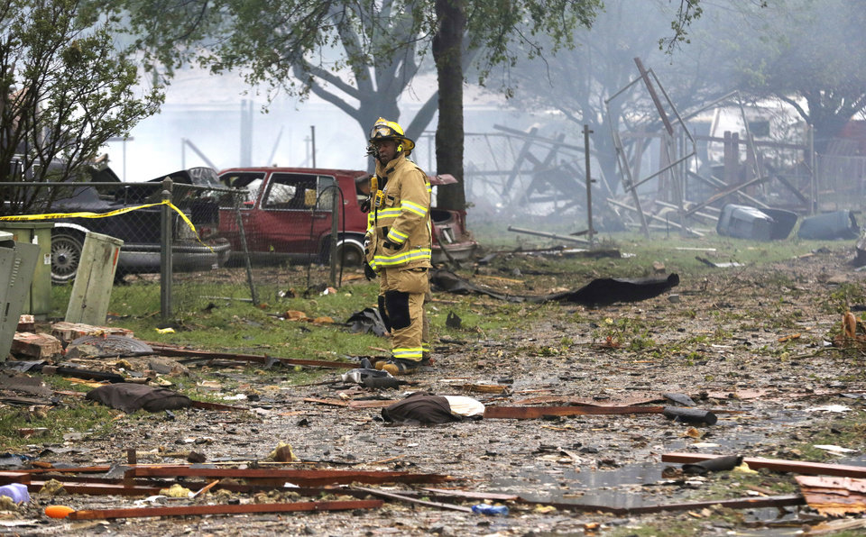 Photo - A firefighter pauses while surveying the blast zone destroyed by an explosion at a fertilizer plant during search and rescue efforts in West, Texas, Thursday, April 18, 2013.  A massive explosion at the West Fertilizer Co. killed as many as 15 people and injured more than 160, officials said overnight.  (AP Photo/LM Otero)