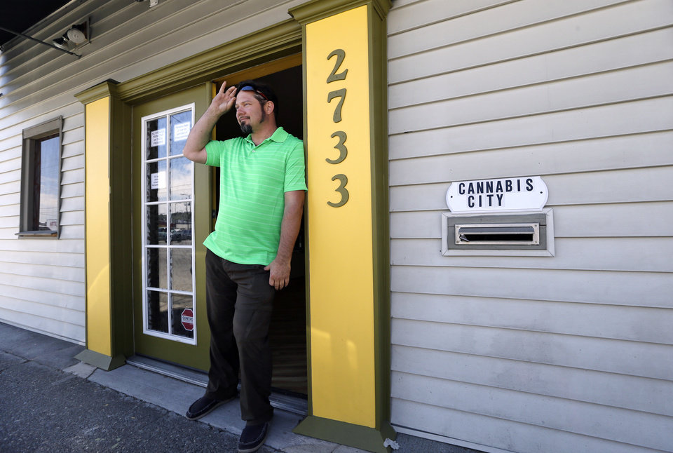 Photo - Cannabis City owner James Lathrop briefly stands outside his business, with a temporary sign over the mail slot, in between media interviews Wednesday, July 2, 2014, in Seattle. Lathrop expects to be begin selling pot Tuesday, July 8, the first day that recreational marijuana can legally be sold in Washington state. Lathrop is expected to be the first licensed retailer in Seattle. (AP Photo/Elaine Thompson)