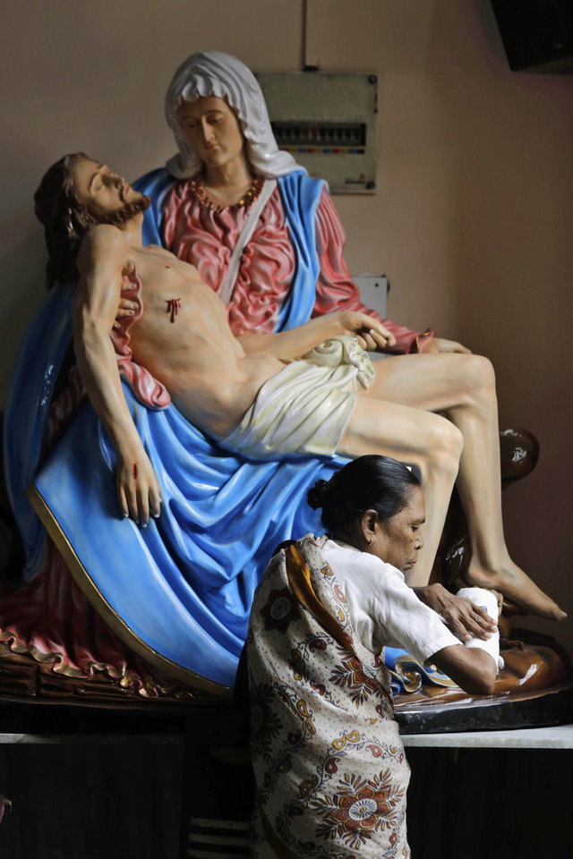 Photo - An Indian Catholic woman touches her fractured hand in the belief that it will heal as she stands in front of a portrait of Mother Mary and Jesus Christ on Good Friday in Kolkata, India, Friday, April 18, 2014. Christians all over the world are marking Good Friday, the day when Christ was crucified. (AP Photo/Bikas Das)