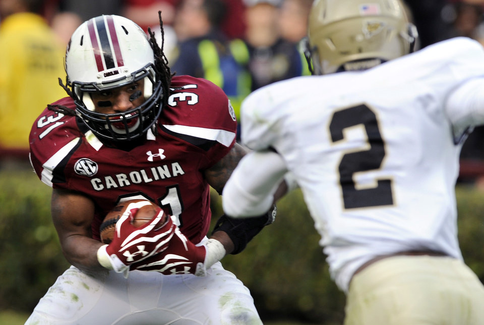 Photo -   South Carolina running back Kenny Miles (31) runs the ball against Wofford cornerback Stephon Shelton (2) during the second half of an NCAA college football game, Saturday, Nov. 17, 2012, in Columbia, S.C. South Carolina defeated Wofford 24-7. (AP Photo/Stephen Morton)