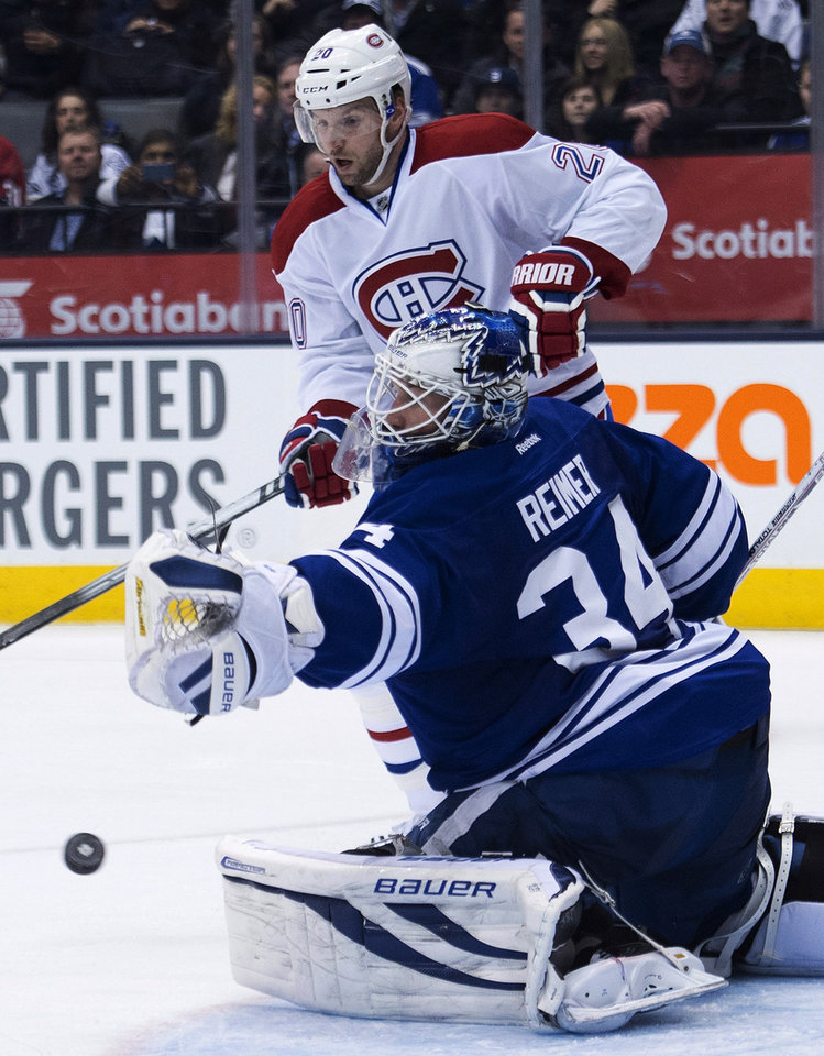Photo - Toronto Maple Leafs' James Reimer, (34) makes a save as Montreal Canadiens forward Thomas Vanek looks on during third period of an NHL hockey game in Toronto on Saturday, March 22, 2014. (AP Photo/The Canadian Press, Nathan Denette)