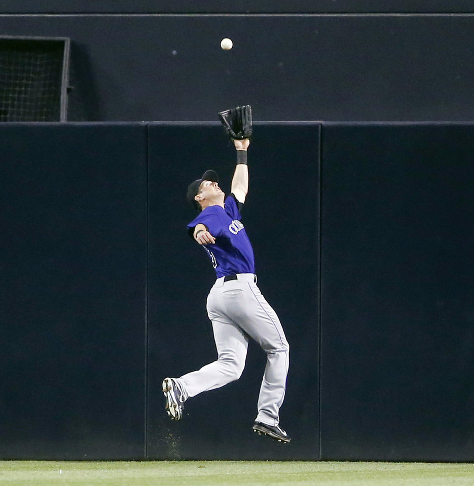 Photo - Colorado Rockies center fielder Drew Stubbs leaps but can't make the catch on a double hit by San Diego Padres' Yasmani Grandal in the fourth inning of a baseball game Monday, Aug. 11, 2014, in San Diego. The double came with Jedd Gyorkoa on first who was thrown out trying to score. (AP Photo/Lenny Ignelzi)