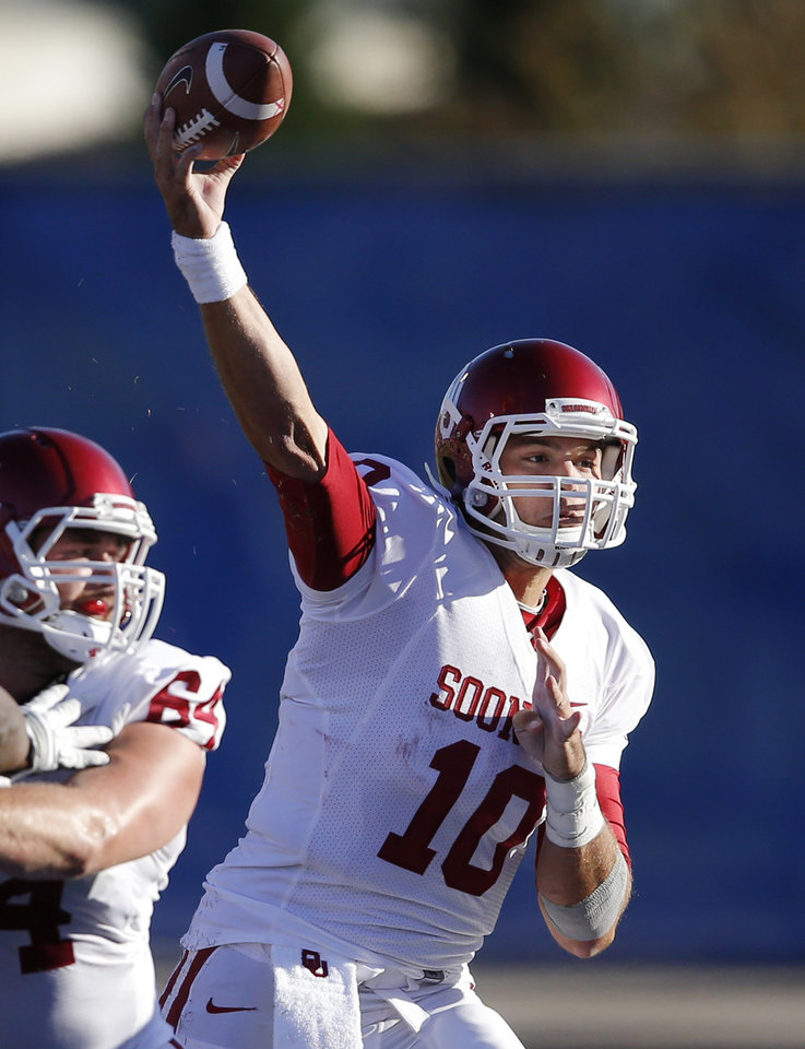 Photo - Oklahoma quarterback Blake Bell (10) passes to a teammate during the second half of an NCAA college football game against Kansas in Lawrence, Kan., Saturday, Oct. 19, 2013. Oklahoma defeated Kansas 34-19. (AP Photo/Orlin Wagner)