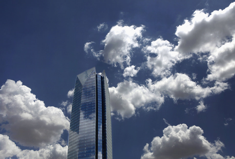 Photo - Fluffy white clouds float across  blue skies over downtown Oklahoma City on a hot July afternoon Monday, July 23, 2012.  The building in the photo is the 50-story tall Devon Energy Tower, the newest skyscraper on the Oklahoma City skyline. Photo by Jim Beckel, The Oklahoman.