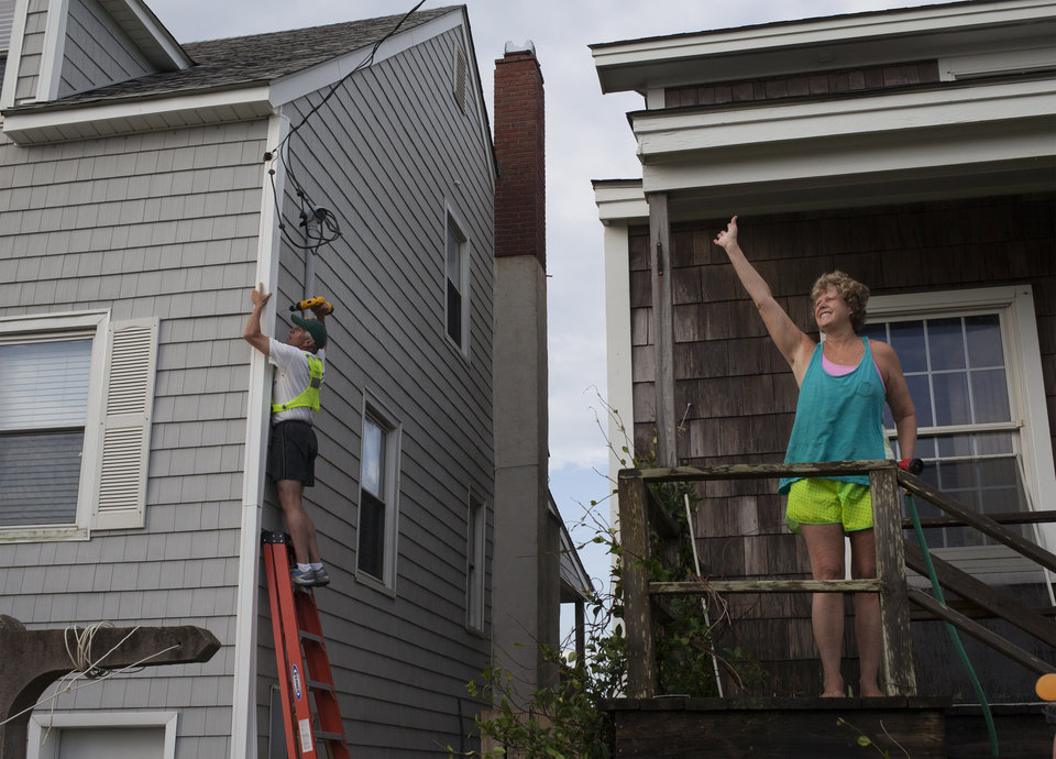 Photo - Missy McGraw, right, of Richmond, Va., waves to a neighbor as her husband, Art, works to repair a cable line on a neighbor's beach house in Atlantic Beach, N.C., Friday, July 4, 2014. Damage was scattered and light along the North Carolina coast near where the eye of Hurricane Arthur came ashore on Thursday evening. (AP Photo/Randall Hill)