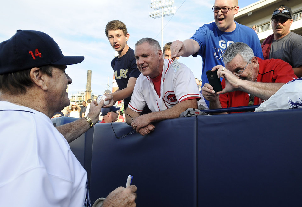 Photo - Pete Rose, left, signs autographs for fans before a game at The Ballpark at Harbor Yard, Monday, June 16, 2014, in Bridgeport, Conn. Rose, banned from Major League Baseball, returned to the dugout for one day to manage the independent minor-league Bridgeport Bluefish. (AP Photo/Jessica Hill)