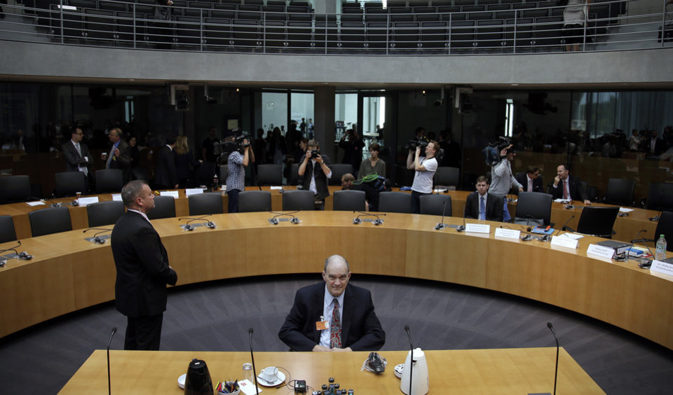 Photo - A police officer stands next to former US National Security Agency, NSA,  employee William Binney, center, as Binney waits for his questioning by the German parliamentary NSA investigation committee in Berlin, Germany, Thursday, July 3, 2014. The committee investigates  the NSA  surveillance  activities, that also included the tapping of German Chancellor Angela Merkel.  (AP Photo/Michael Sohn)