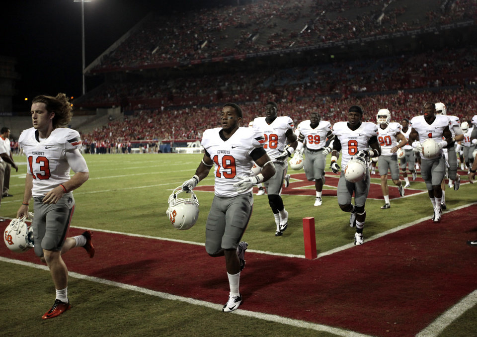 Photo - Oklahoma State runs off the field after warm ups before the college football game between the University  of Arizona and Oklahoma State University at Arizona Stadium in Tucson, Ariz.,  Thursday, Jan. 17, 2008. Photo by Sarah Phipps, The Oklahoman