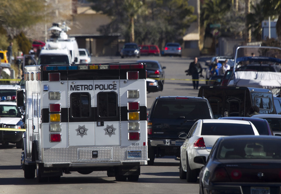 Law enforcement officials investigate a shooting and fire in Boulder City, Nev., Monday, Jan. 21, 2013. Las Vegas police spokeswoman Carla Alston confirmed that a Las Vegas police officer was involved in the 9 a.m. Monday incident and says Henderson police are handling the investigation. (AP Photo/Las Vegas Sun, Steve Marcus)