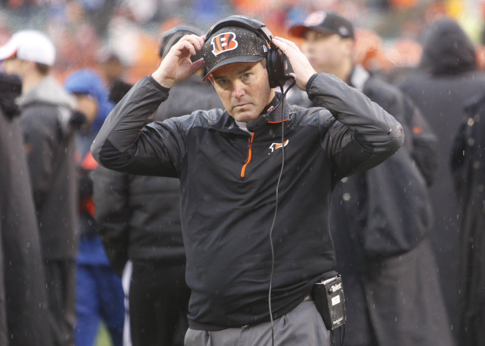 Photo - FILE - IN this Jan. 5, 2014 file photo, Cincinnati Bengals defensive coordinator Mike Zimmer adjusts his head set in the second half of an NFL wild-card playoff football game against the San Diego Chargers, in Cincinnati. The Minnesota Vikings have chosen Zimmer as their new head coach, according to multiple media reports. Zimmer will replace Leslie Frazier, who was fired after the team finished 5-10-1 this season. (AP Photo/David Kohl, File)