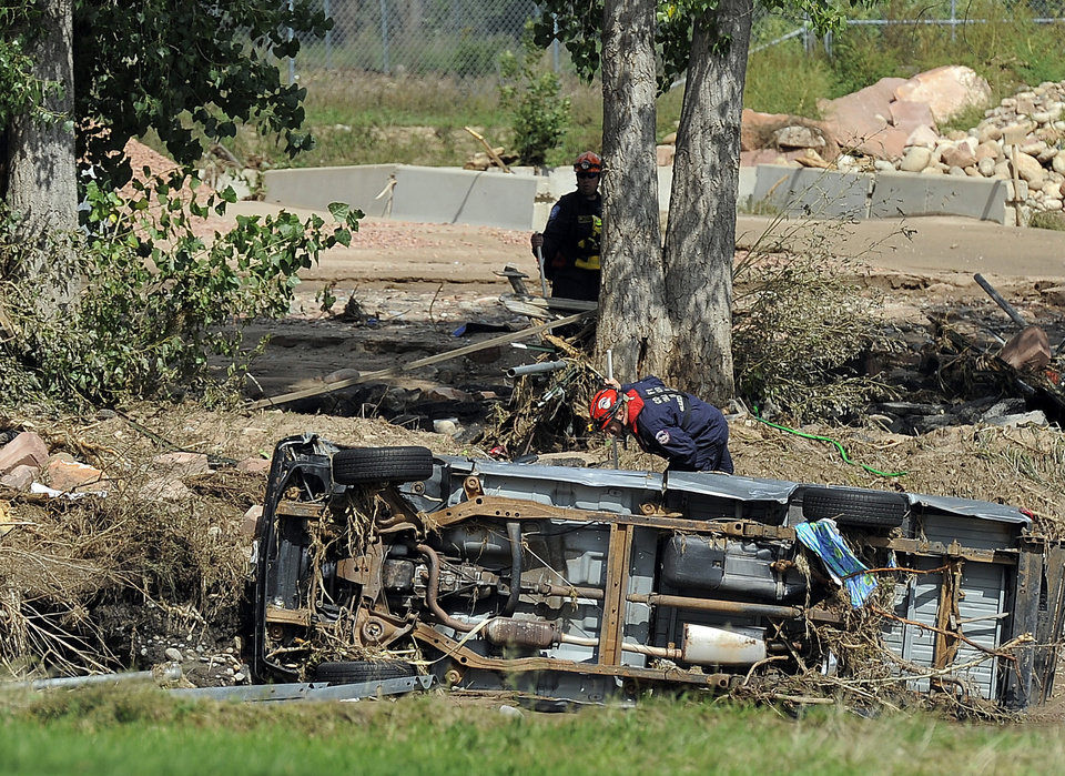Photo - A member of a search and rescue team looks beneath an overturned car in Lyons, Colo., on Thursday, Sept. 19, 2013. The recovery process has begun all along the front range as people clean out flooded homes and businesses.  (AP Photo/Chris Schneider)