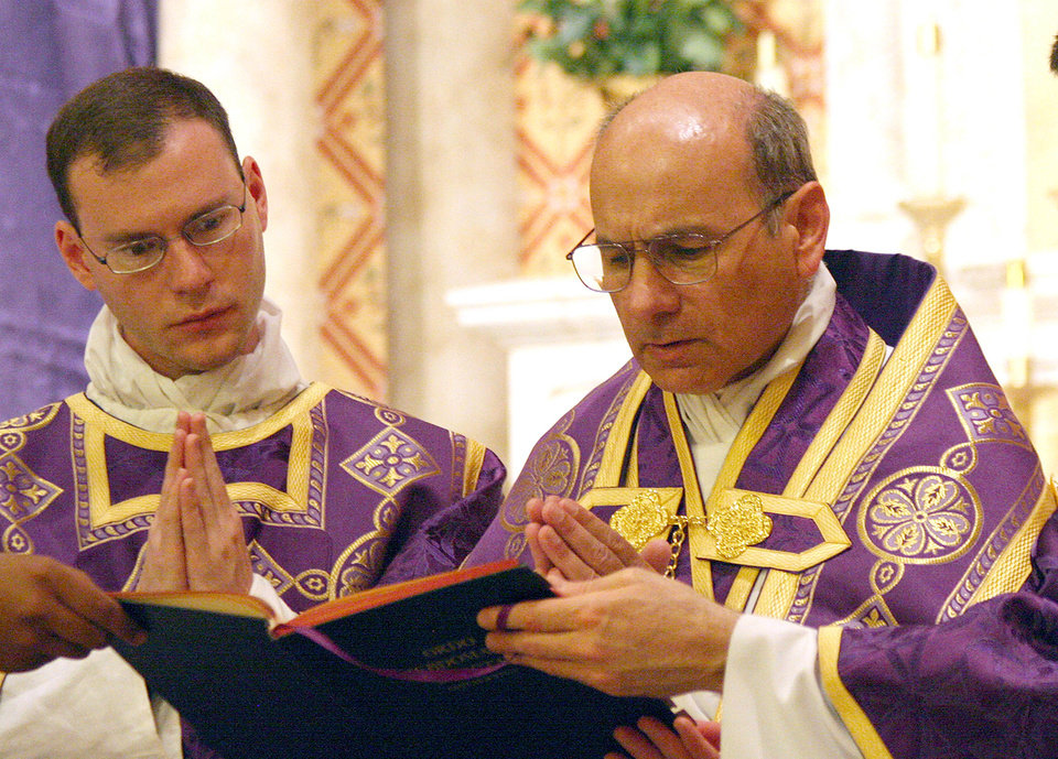 Photo - In this photo provided by The Catholic Sun, date not known, the Rev. Kenneth Walker, left, and the Rev. Joseph Terra perform a Mass in Phoenix. Walker was killed and Terra was critically injured during a robbery attempt at Mother of Mercy Mission church on Wednesday, June 11, 2014. (AP Photo/The Catholic Sun)