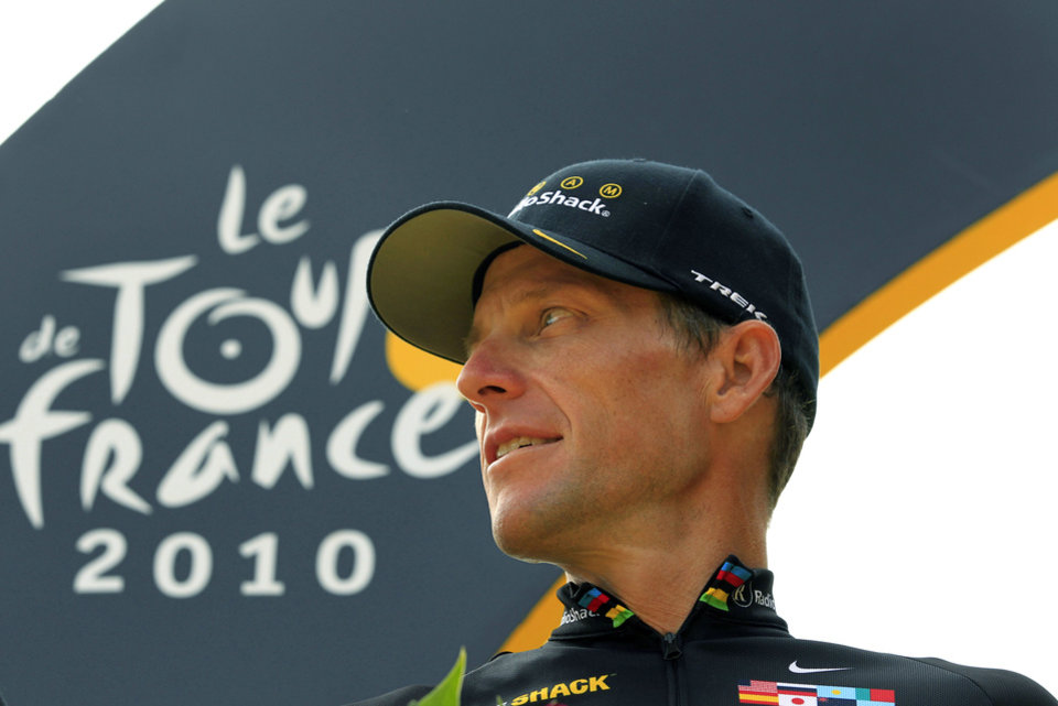Photo - FILE - In this July 25, 2010, file photo, Lance Armstrong looks back on the podium after the 20th and last stage of the Tour de France cycling race in Paris, France. Armstrong confessed to using performance-enhancing drugs to win the Tour de France during a taped interview with Oprah Winfrey that aired Thursday, Jan. 17, 2013, reversing more than a decade of denial. (AP Photo/Bas Czerwinski, File)