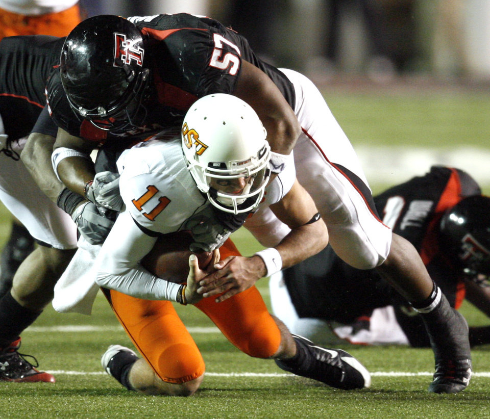 Photo - Zac Robinson is brought down on a keeper by Brian Duncan (57) during the second half of the college football game between the Oklahoma State University Cowboys (OSU) and the Texas Tech Red Raiders at Jones AT&T Stadium on Saturday, Nov. 8, 2008, in Lubbock, Tex.  Texas tech won 56-20.By Steve Sisney/The Oklahoman