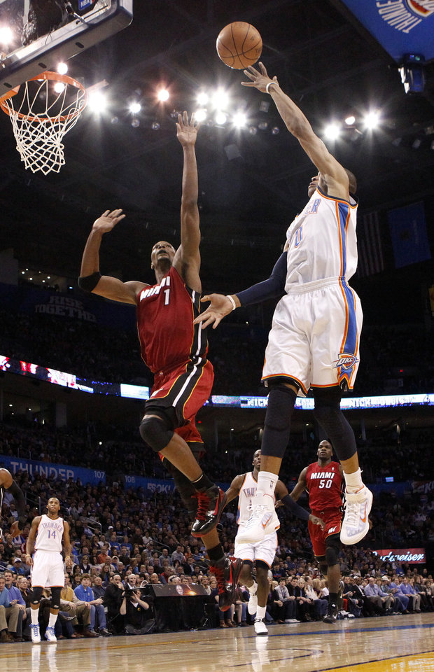 Oklahoma City\'s Russell Westbrook (0) shoots as Miami\'s Chris Bosh (1) tries to block the shot during the NBA basketball game between Oklahoma City and Miami at the OKC Arena in Oklahoma City, Thursday, Jan. 30, 2011. Photo by Sarah Phipps, The Oklahoman