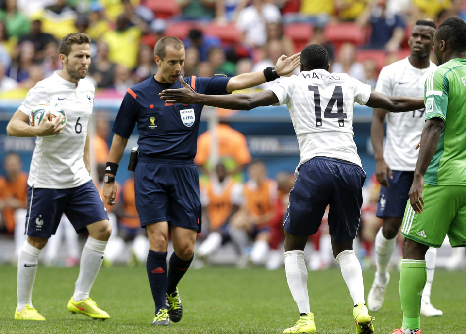 Photo - Referee Mark Geiger from the U.S marks a fail to France's Blaise Matuidi (14) during the World Cup round of 16 soccer match between France and Nigeria at the Estadio Nacional in Brasilia, Brazil, Monday, June 30, 2014. At left is France's Yohan Cabaye.(AP Photo/Ricardo Mazalan)