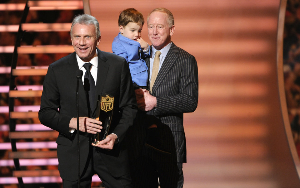 Photo - Former NFL player Joe Montana speaks as he presents the award for AP Most Valuable Player, as Archie Manning holds his grandson Marshall Manning at the third annual NFL Honors at Radio City Music Hall on Saturday, Feb. 1, 2014, in New York. Archie Manning accepted on behalf of his son Peyton. (Photo by Evan Agostini/Invision for NFL/AP Images)
