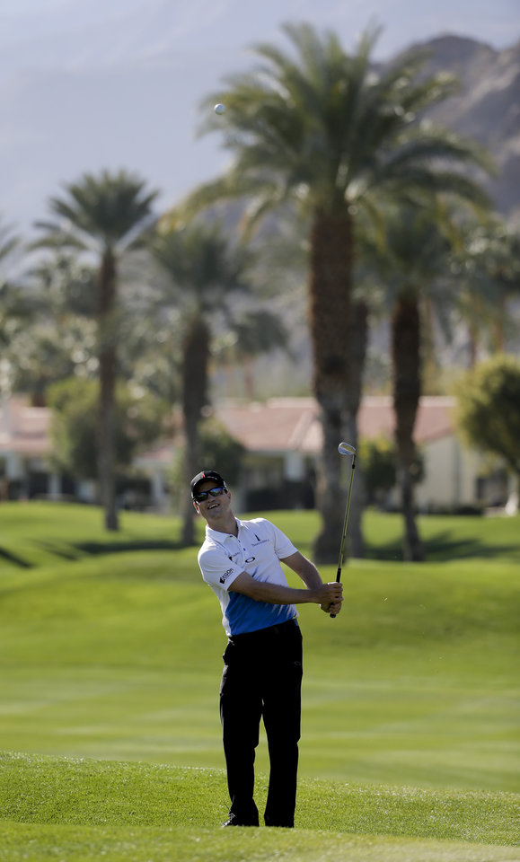 Photo - Zach Johnson hits shots around the 11th green during a practice round for the Humana Challenge golf tournament on the Palmer Private course at PGA West, Wednesday, Jan. 15, 2014, in La Quinta, Calif. (AP Photo/Chris Carlson)