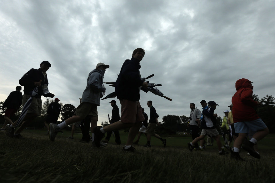Photo - Spectators head of the course as a weather warning delays the first round of the U.S. Open golf tournament at Merion Golf Club, Thursday, June 13, 2013, in Ardmore, Pa. (AP Photo/Charlie Riedel)