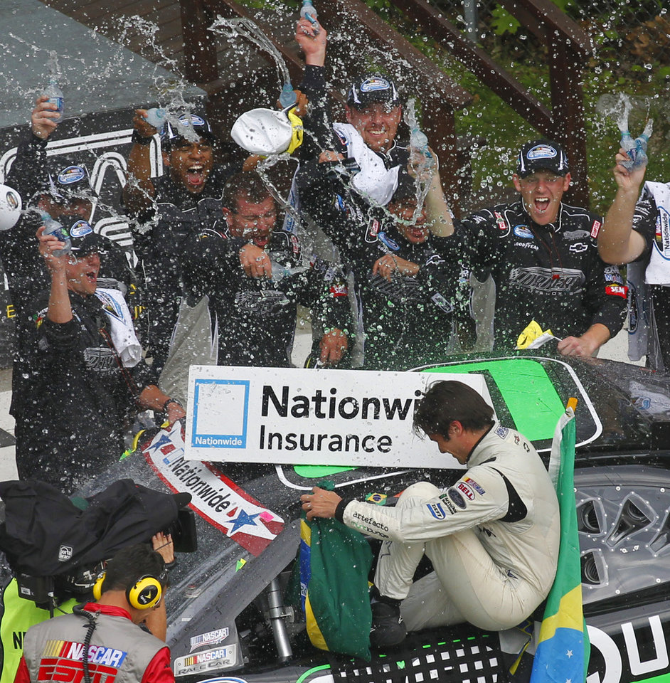 Photo -   Nelson Piquet Jr. gets sprayed by his race crew as he gets out of his car in victory lane after winning the NASCAR Nationwide Series Sargento 200 auto race at Road America in Elkhart Lake, Wis, Saturday, June, 23, 2012. (AP Photo/Jeffrey Phelps)