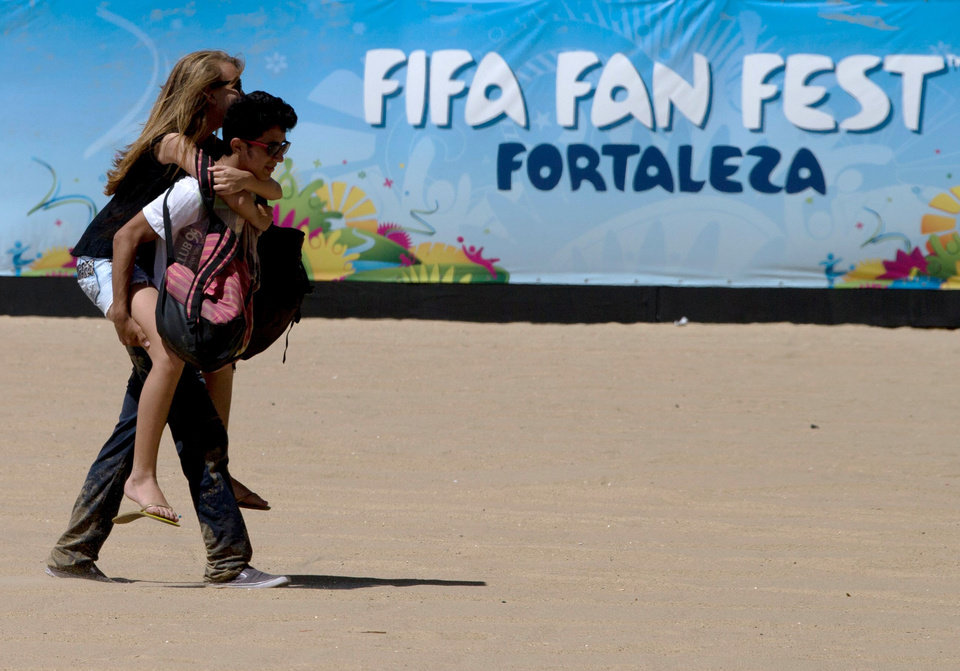A couple walk by a sign promoting the FIFA soccer fan fest complex in Fortaleza, Brazil, Tuesday, June 10, 2014. With the World Cup opening on the same date Brazil traditionally celebrates its version of Valentine's Day, June 12, merchants are helping lovers and spouses figure out how to embrace both. (AP Photo/Fernando Llano)