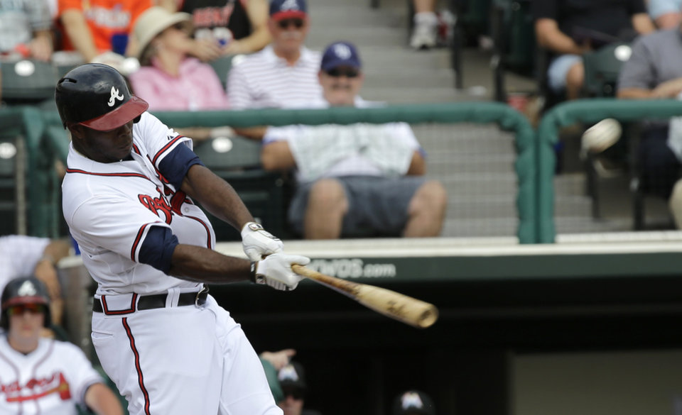 Photo - Atlanta Braves' Justin Upton hits a home run against the Miami Marlins during the fourth inning of an exhibition spring training baseball game Monday, Feb. 25, 2013, in Kissimmee, Fla. (AP Photo/David J. Phillip)