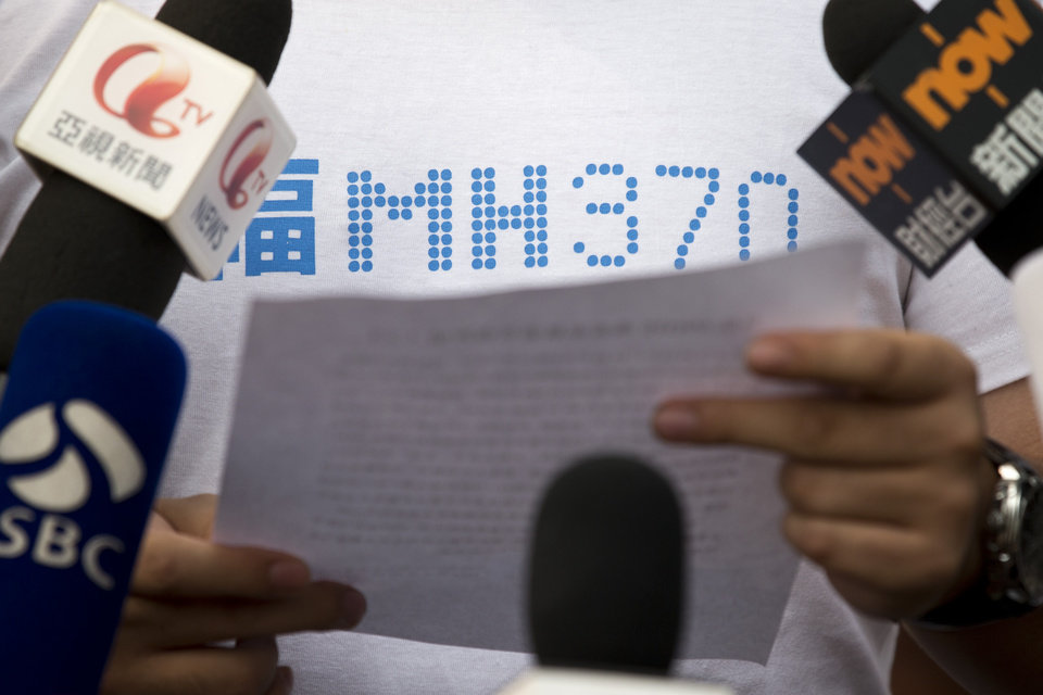 Photo - A representative of relatives of Chinese passengers onboard Malaysia Airlines Flight 370, center, makes an announcement to journalists prior to a briefing with Malaysian officials at a hotel in Beijing, China, Wednesday, March 26, 2014. About two-thirds of the missing, 239 people onboard, are Chinese, and their relatives have lashed out at Malaysia for essentially declaring their family members dead without any physical evidence of the plane's remains. (AP Photo/Alexander F. Yuan)