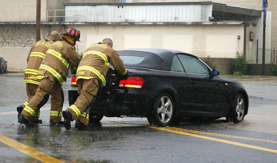 Photo - Firefighters from Station One help to push a stalled car off the roadway at Broadway and 21st St. in Oklahoma City, OK, Monday, June 14, 2010. By Paul Hellstern, The Oklahoman