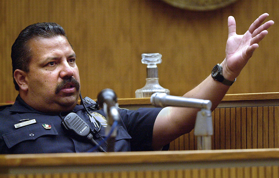 Photo - FILE - In this May 10, 2001, file photo, El Cajon, Calif., Police department school resource officer Rich Agundez Jr., who confronted and wounded a student who attacked Granite Hills High School with a shotgun in 2001, testifies in El Cajon. The National Rifle Association's response to a Connecticut school massacre envisions, in part, having trained, armed volunteers in every school in America. But Agundez, school safety experts and school board members say there's a huge difference between a trained law enforcement officer who becomes part of the school family _ and a guard with a gun.  (AP Photo/U-T San Diego, John Gastaldo)  SAN DIEGO COUNTY OUT; NO SALES; COMMERCIAL INTERNET OUT; FOREIGN OUT