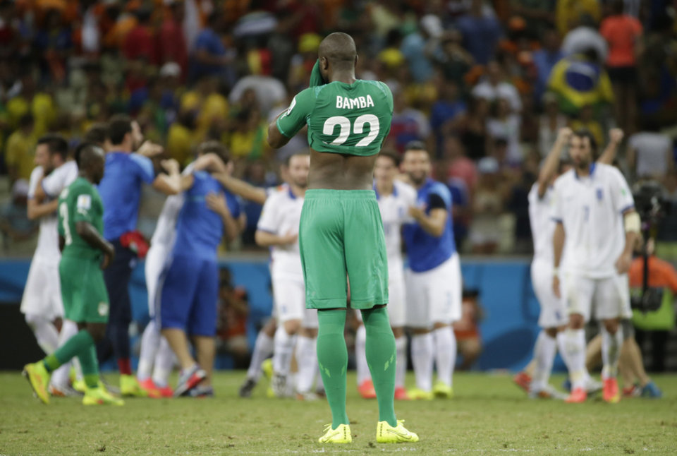 Photo - Ivory Coast's Sol Bamba wipes his face after his teams lost 1-2 in the group C World Cup soccer match between Greece and Ivory Coast at the Arena Castelao in Fortaleza, Brazil, Tuesday, June 24, 2014. (AP Photo/Fernando Llano)