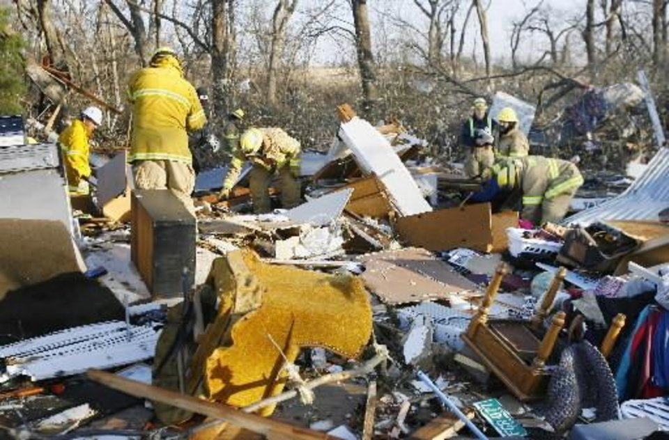 Photo - Lone Grove firemen search a home for unaccounted for people on the north side of SH 70 in Lone Grove Wednesday, Feb. 11, 2009. BY  PAUL B.  SOUTHERLAND