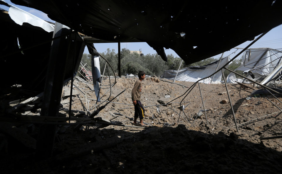Photo - Palestinians inspect the rubble of a house after it was hit by an Israeli missile strike in Rafah, southern Gaza Strip, Sunday, July 6, 2014. The Israeli airstrikes targeted what the army said were militant sites including rocket launchers and a weapons manufacturing site, following at least 29 other rockets and mortar shells fired from the Gaza Strip at Israel over the weekend. (AP Photo/Hatem Moussa)