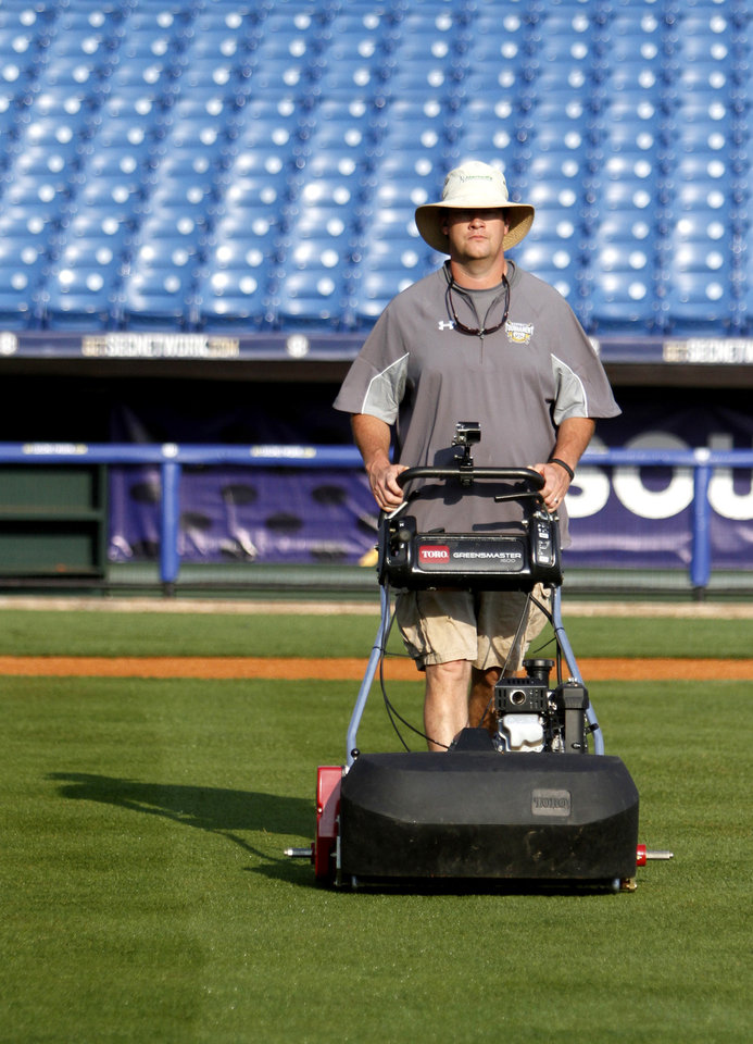 Photo - In this May 22, 2014 photo, Dan Bergstrom, head groundskeeper of the Houston Astros, cuts the infield grass at the Southeastern Conference NCAA college baseball tournament in Hoover, Ala. A 40-man grounds crew that includes Bergstrom labored to keep the Hoover Met's field in good shape. Bergstrom was able to work the tournament since the Astros were on the road. (AP Photo/Butch Dill)