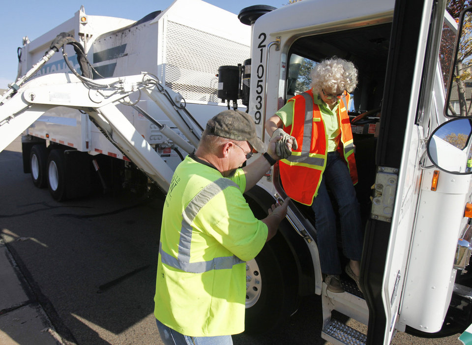 Right: Former mayor Saundra Naifeh, president of Edmond Beautiful, is helped from the truck by Jeff Whitfield, Edmond sanitation truck driver. Naifeh and other members of Edmond Beutiful rode on trash trucks Friday.  PHOTO BY PAUL HELLSTERN,  THE OKLAHOMAN