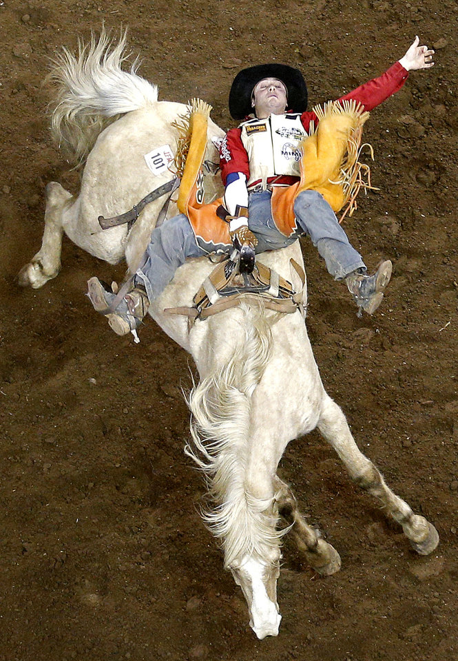 Photo - Philppe Harvey of Terre Bonne, Quebec rides in the bareback bronc event during the International Finals Rodeo at the State Fair Arena in Oklahoma City, Friday, Jan. 17, 2014.  Photo by Sarah Phipps, The Oklahoman