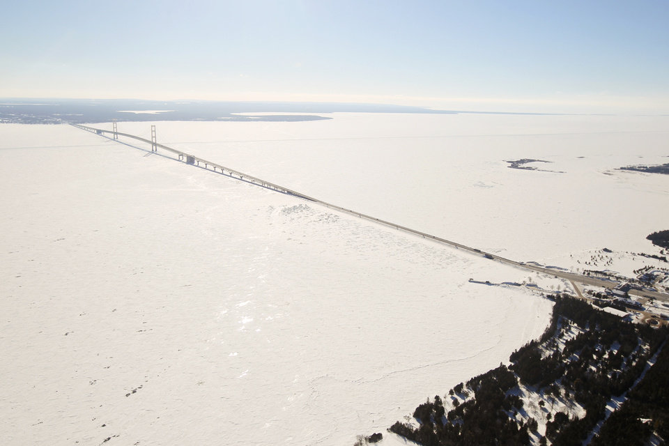 Photo - POOL PHOTO -- In this Feb. 11, 2014 aerial photo the Mackinac Bridge over the the Straits of Mackinac spans an ice cover that stretches into the horizon in Michigan. As of Feb. 13, the ice cover extended across 88 percent of the Great Lakes and almost completely covered, according to the federal government's Great Lakes Environmental Research Laboratory in Ann Arbor. (AP Photo/ Traverse City Record-Eagle, Keith King Pool)
