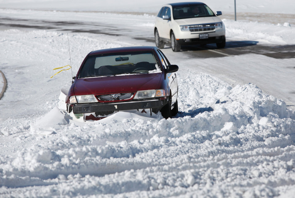 Photo - An abandoned car at an intersection near Memorial and Kelly in Oklahoma City.Central Oklahoma residents began digging out from beneath nearly a foot of snow covering the ground Wednesday, Feb, 2, 2011, after yesterday's winter snowstorm. Photo by Jim Beckel, The Oklahoman