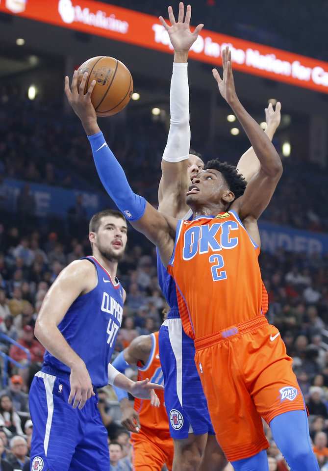 Photo - Oklahoma City's Shai Gilgeous-Alexander (2) goes the basket beside LA's Ivica Zubac (40) and Landry Shamet (20) during an NBA basketball game between the Oklahoma City Thunder and the LA Clippers at Chesapeake Energy Arena in Oklahoma City, Sunday, Dec. 22, 2019. [Bryan Terry/The Oklahoman]