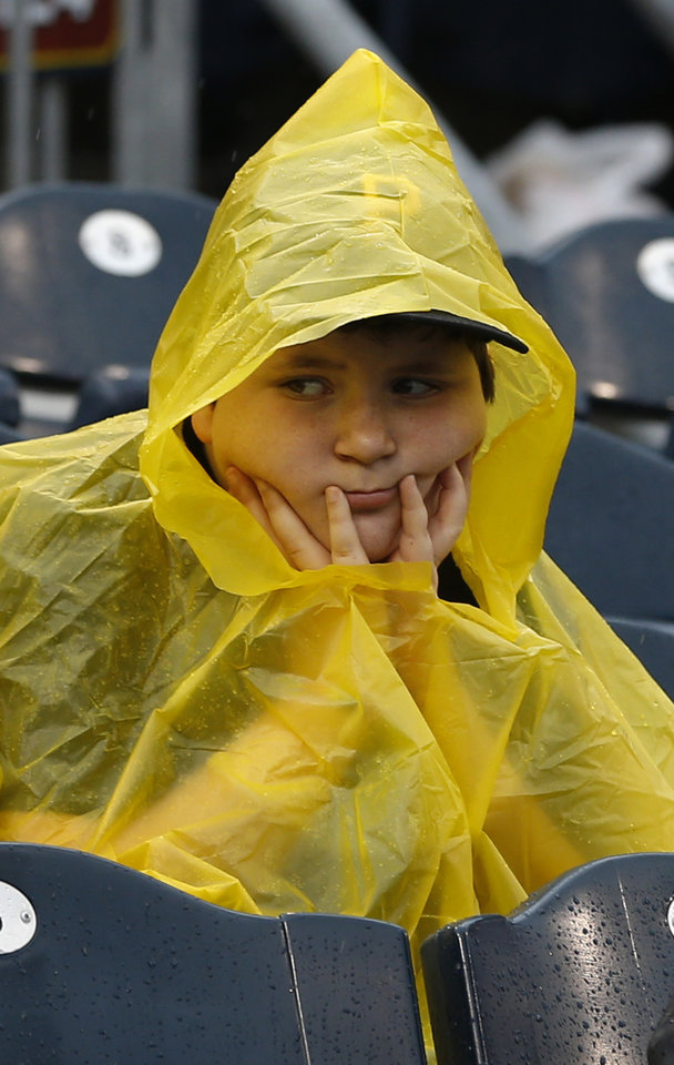 Photo - A young baseball fan wears a yellow poncho as he waits out a rain delay in the baseball game between the Pittsburgh Pirates and the Milwaukee Brewers on Sunday, June 30, 2013, in Pittsburgh. (AP Photo/Keith Srakocic)