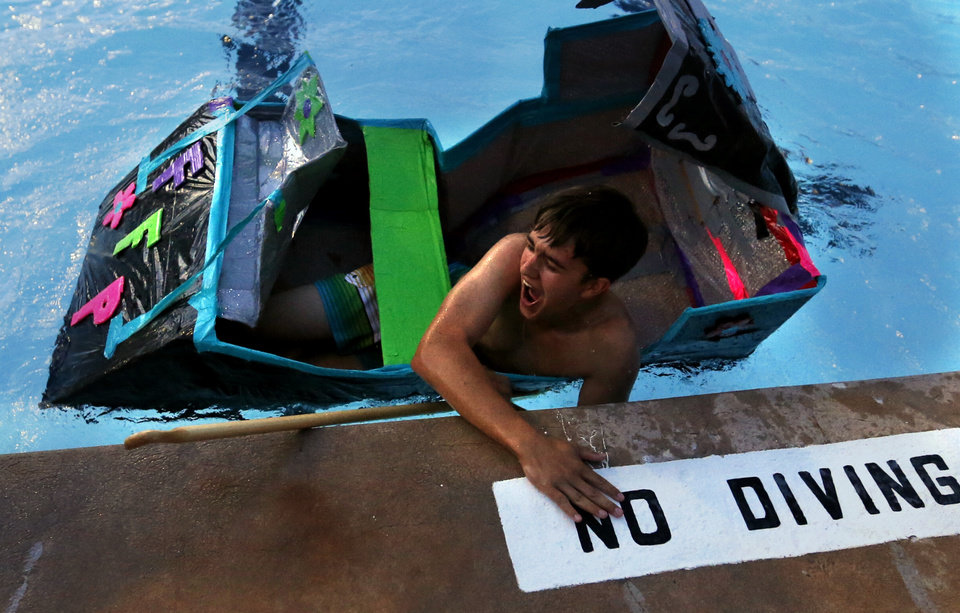 Photo -  Thomas Owens, a Heritage Hall senior from Edmond, touches the finish line after swimming with his self-designed boat after tipping over in the cardboard regatta at the University of Oklahoma's summer engineering camp. PHOTO BY STEVE SISNEY, THE OKLAHOMAN   STEVE SISNEY -