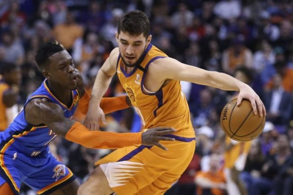 Photo -  Thunder guard Dennis Schroeder, left, attempts to steal the ball from Suns guard Ty Jerome during the first half of OKC's 111-107 win Friday. [AP Photo/Ross D. Franklin]