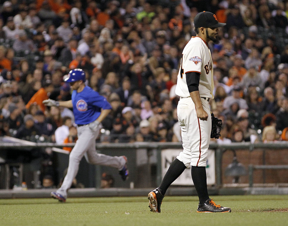 Photo - San Francisco Giants relief pitcher Sergio Romo walks back to the mound as Chicago Cubs' Nate Schierholtz rounds the bases after hitting a solo home run during the ninth inning of a baseball game Saturday, July 27, 2013, in San Francisco. (AP Photo/Tony Avelar)